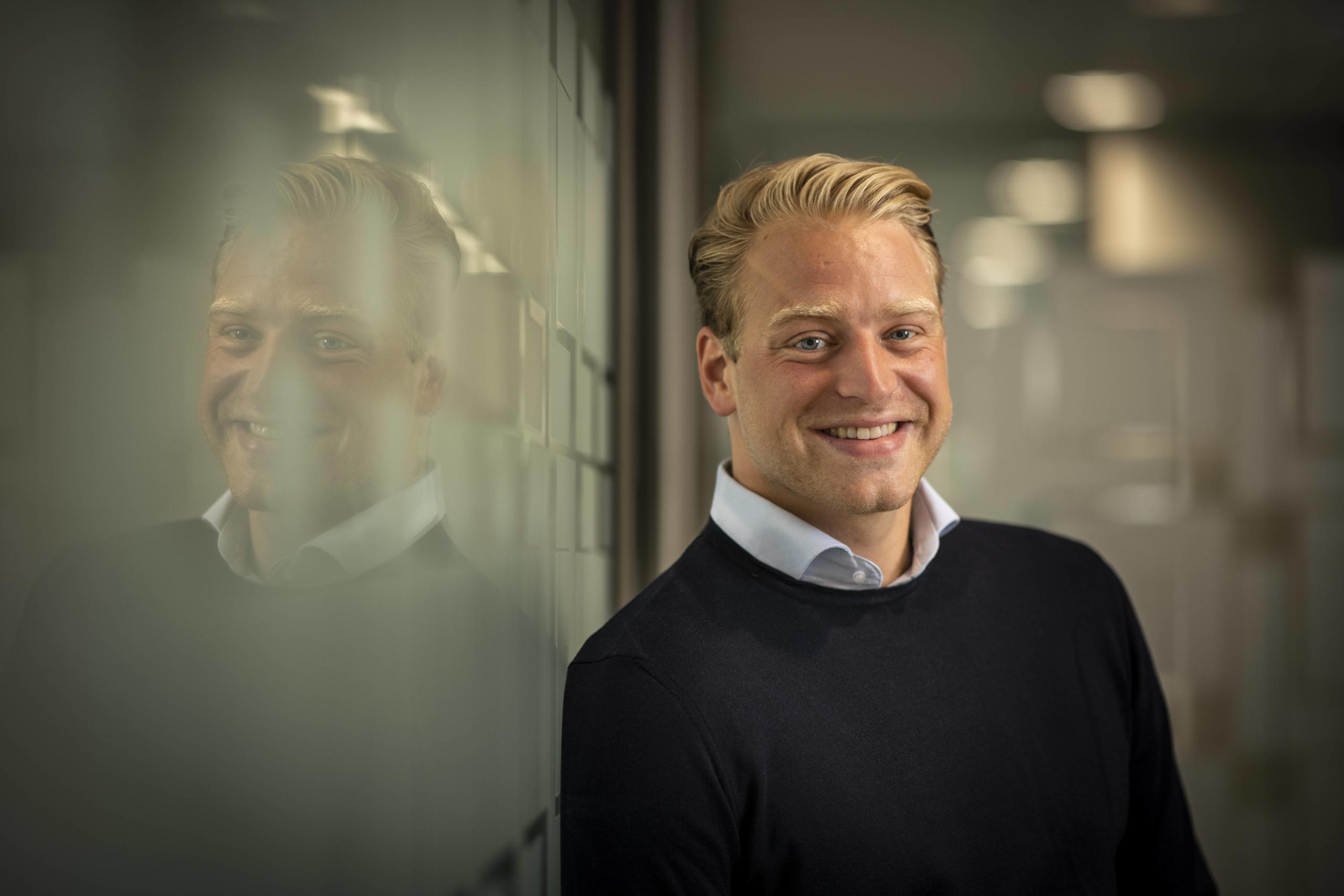 Benjamin Maas bij Bluefield op kantoor naast glazen wand